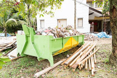Construction rubbish bin with loads at construction site. Royalty Free Stock Images
