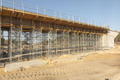 Construction scaffolding built under an overpass over the highw Royalty Free Stock Image