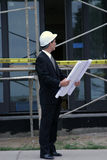 Construction series. A business man, or contractor or architect or building inspector inspects the work and blue prints on new home construction Royalty Free Stock Photo