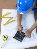 Construction series. Construction engineer working on blueprints Stock Photography