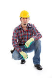 Construction Series. A construction worker squats down and grins for the camera royalty free stock images