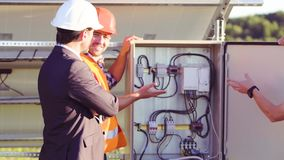 Construction of the shield. Two man is special uniform working on construction solar energy station. Standing at the shield and discussing working processes stock footage