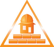 Construction sign. A triangular sign with a house brick, and helmet Stock Photo