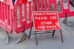 Construction sign standing on footpath Royalty Free Stock Photo