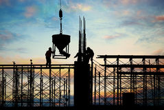 Construction silhouette. Silhouette of hardworking men on construction site Stock Photo
