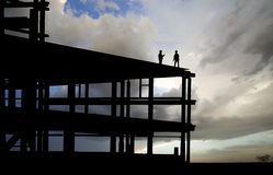 Construction Silhouette. Two workers standing on top of a construction zone Royalty Free Stock Images