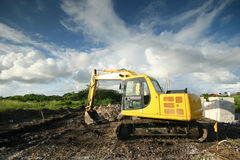 Construction site. A yellow mechanical digger on a construction site stock photos