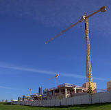 Construction site. With yellow cranes over blue sky and green grass Stock Image
