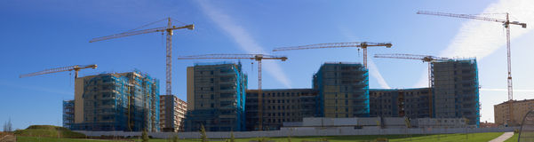 Construction site. With yellow cranes over blue sky behind green grass Stock Photography