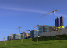 Construction site. With yellow cranes over blue sky and green grass Stock Images