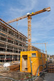 Construction site. Large construction site with scaffolding building, tower crane and clear blue sky Royalty Free Stock Photos