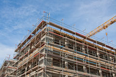 Construction site. Large construction site with scaffolding building, tower crane and clear blue sky Stock Image