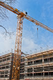 Construction site. Large construction site with scaffolding building, tower crane and clear blue sky Royalty Free Stock Photo