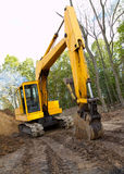 Construction site. Older excavator hoe machine on muddy construction site with billowing diesel smoke exhaust stock photos