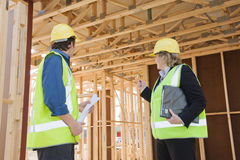 At the construction site. Civil engineer and worker discussing issues at the construction site .Focus on  the rear Royalty Free Stock Images