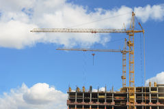 Construction site. Two yellow cranes on construction site against cloudy sky Stock Image