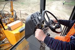 Construction site. Driving a grader at construction site, real people Stock Image