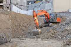 Construction Site. Horizontal photo of a construction site. There is an orange excavator loading machine. This is the foundation of a building. Everything is Stock Photos