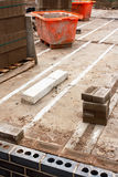 Construction site. Builders construction site with waste bins and partly constructed cavity walls Royalty Free Stock Photo