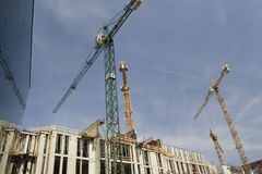 Construction Site. With cranes and blue sky next to modern glass front building Stock Image