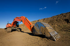 Construction site. A large orange backhoe at a construction site Royalty Free Stock Photos