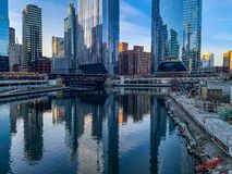 Construction site alongside still waters of Chicago River. Which are reflecting surrounding cityscape royalty free stock image