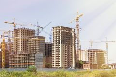 Construction Site Background. Hoisting Cranes And New Multi-storey Buildings. Tower Crane And Unfinished High-rise Building. Many Royalty Free Stock Photography