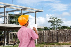 Construction site. A boy wearing engineers cap and stand at construction site of concrete building Royalty Free Stock Photos