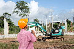Construction site. A boy wearing engineers cap and stand at construction site of concrete building Stock Image