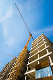 Construction site with building with crane and blue sky Stock Images