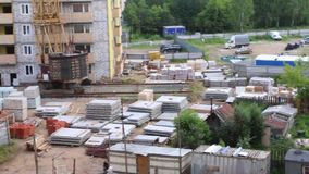 Construction site with building materials, part of crane at summer day stock video