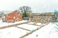 New Home Building. Construction site building a new brick home during winter time, snowing conditions royalty free stock photos