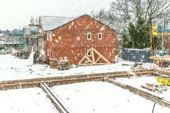 New Home Building. Construction site building a new brick home during winter time, snowing conditions royalty free stock photo