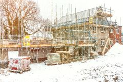 New Home Building. Construction site building a new brick home during winter time, snowing conditions royalty free stock photography