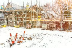 New Home Building. Construction site building a new brick home during winter time, snowing conditions stock photography
