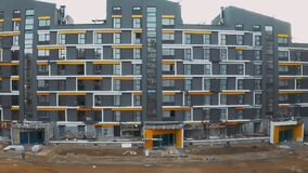 Construction site, building work process modern an apartment panel house. Cladding of facades block of flats. Aerial