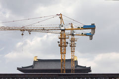 Construction site in China. Construction site with two high cranes on the foreground an a rooftop of a traditional Chinese building on the background Stock Images