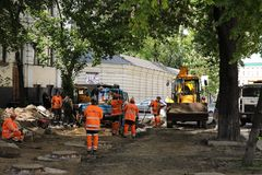 Kyiv/Ukraine - 18 may 2019:Construction site with communal service workers in orange uniform and construction machinery stock photos