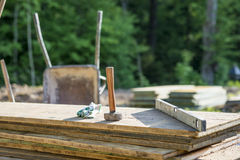 Construction Site concept with a wooden mallet, level and gloves. On planks of wood outdoors in a forested area Stock Photography