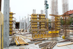Construction Site. Concrete pillars supported with yellow boards and metal rods on construction site Stock Photo