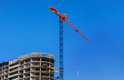 Construction site. Construction crane and high-rise building under construction against blue sky. Stock Photo