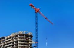 Construction site. Construction crane and high-rise building under construction against blue sky. Stock Photos