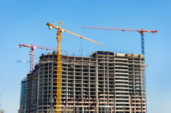 Construction site. Construction cranes and high-rise building under construction against blue sky. Royalty Free Stock Photos