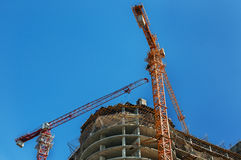 Construction site. Construction cranes and high-rise building under construction against blue sky. Stock Image