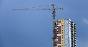 Construction cranes and high-rise building under construction against blue sky. Royalty Free Stock Photo