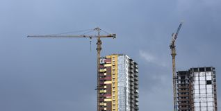 Construction cranes and high-rise building under construction against blue sky. Royalty Free Stock Images
