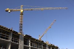 Construction cranes and high-rise building under construction against blue sky. Construction site. Construction cranes and high-rise building under construction Royalty Free Stock Photos