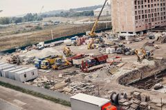 Construction Site, construction machinery, bulldozer, excavation. Factory,  cranes and sand. house building area in the city. brick walls and pit holes and Royalty Free Stock Images