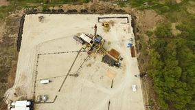 Construction site covered with sand and crane. Beautiful upper view empty construction site covered with sand and tower crane against plowed fields and woods stock footage