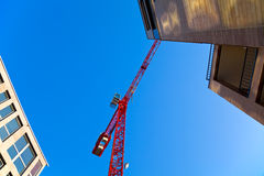 Construction Site with Crane. Construction site with a red crane and two buildings. Copyspace Stock Photos